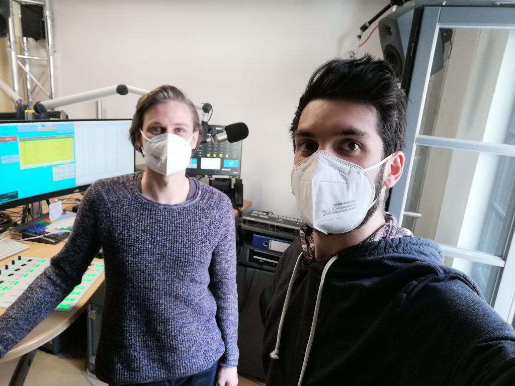 Valentin Weber und Sebastian Schroth machen ein Selfie mit dem Studio im Hintergrund.